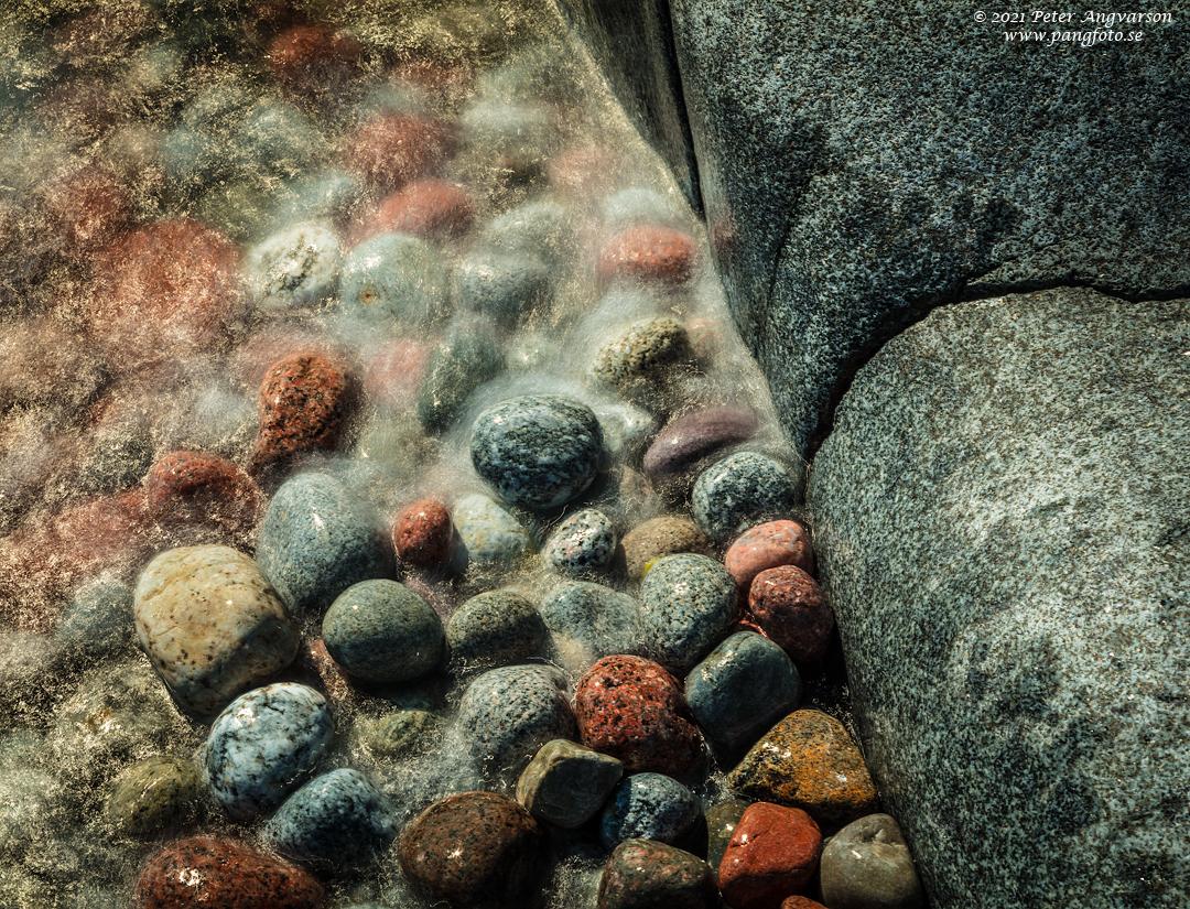 Vatten skäljer över stenar på strand som finns på Trysunda, Höga Kusten.