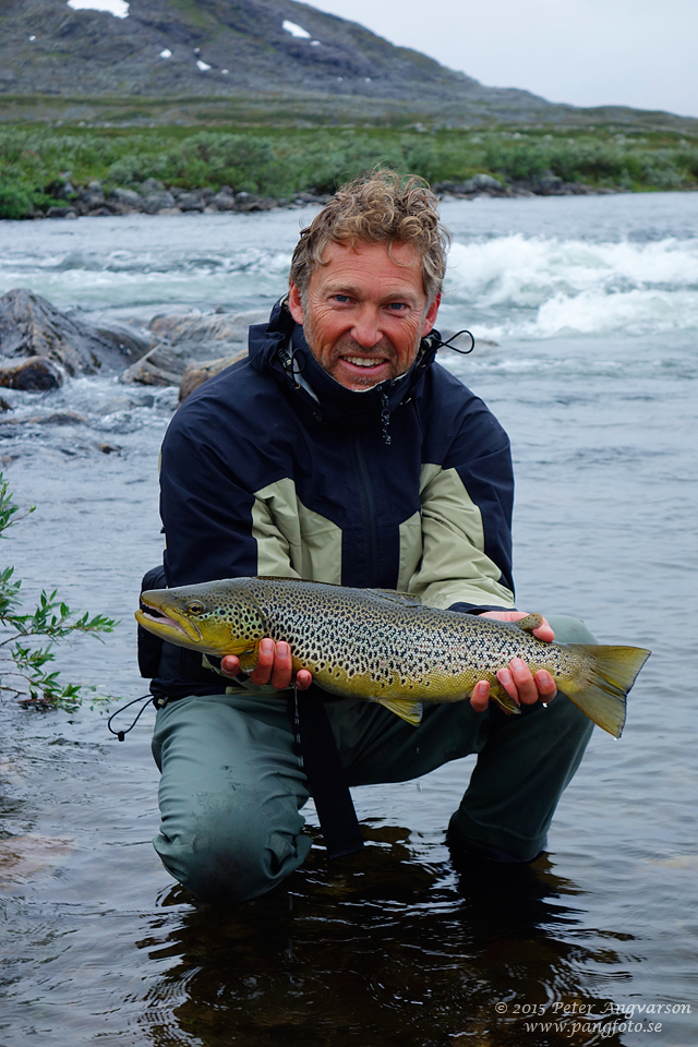 Krister med en av sina fina öringar. Man kan lyfta fisken en kort stund för att ta en bild innan den får återhämta sig i vattnet och sedan simma iväg.
